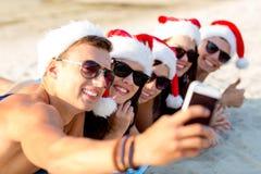 Groupe d'amis dans des chapeaux de Santa avec le smartphone Image stock