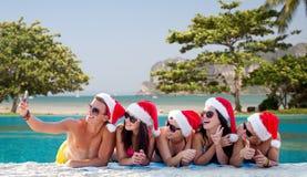 Groupe d'amis dans des chapeaux de Santa avec le smartphone Images libres de droits