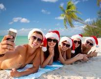 Groupe d'amis dans des chapeaux de Santa avec le smartphone Photographie stock