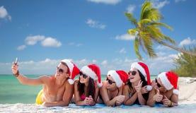 Groupe d'amis dans des chapeaux de Santa avec le smartphone Image libre de droits