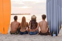 Groupe d'amis dans des lunettes de soleil avec des ressacs sur la plage Image stock