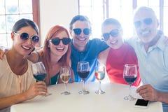 Groupe d'amis dans des lunettes de soleil posant avec des boissons Photos libres de droits