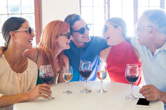 Groupe d'amis dans des lunettes de soleil riant dans le restaurant Images libres de droits