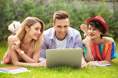 Groupe d'amis dans des vêtements élégants avec l'ordinateur portable Photos libres de droits