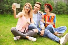 Groupe d'amis dans des vêtements élégants prenant le selfie Image libre de droits