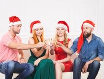 Groupe d'amis dans la célébration de chapeaux de Noël Photographie stock