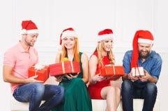 Groupe d'amis dans la célébration de chapeaux de Noël Image stock