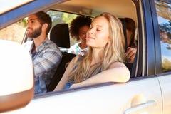 Groupe d'amis dans la voiture sur le voyage par la route ensemble Photographie stock libre de droits