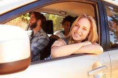 Groupe d'amis dans la voiture sur le voyage par la route ensemble Photos stock