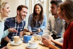 Groupe d'amis dans le ½ de ¿ de Cafï utilisant des dispositifs de Digital Photo stock