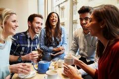 Groupe d'amis dans le ½ de ¿ de Cafï utilisant des dispositifs de Digital Photographie stock