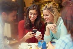 Groupe d'amis dans le ½ de ¿ de Cafï utilisant des téléphones portables Image libre de droits