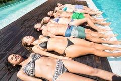 Groupe d'amis dans les vêtements de bain détendant au poolside Image stock