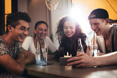 Groupe d'amis dans un café regardant le téléphone portable Photos stock