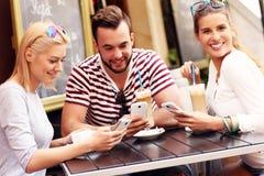 Groupe d'amis dans un café utilisant des smartphones Images libres de droits