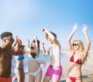 Groupe d'amis dansant sur la plage Images stock