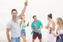 Groupe d'amis dansant sur la plage avec des bouteilles à bière Photo stock
