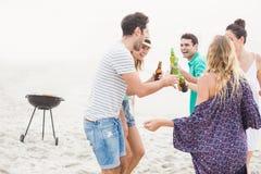 Groupe d'amis dansant sur la plage avec des bouteilles à bière Photo libre de droits