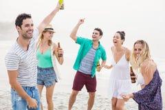 Groupe d'amis dansant sur la plage avec des bouteilles à bière Image libre de droits