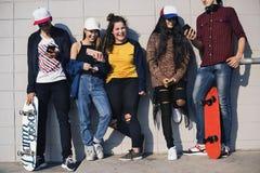 Groupe d'amis de mode de vie adolescent dehors et de concept social de media Image stock