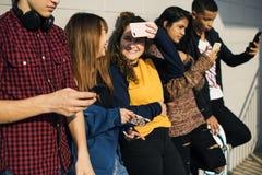 Groupe d'amis de mode de vie adolescent dehors et de concept social de media Photographie stock libre de droits