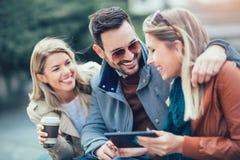 Groupe d'amis de sourire à l'aide du comprimé numérique Photos stock