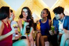 Groupe d'amis de sourire agissant l'un sur l'autre tout en ayant le cocktail Photo stock