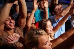 Groupe d'amis de sourire au concert dans le club Image libre de droits