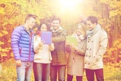 Groupe d'amis de sourire avec des comprimés en parc Images stock