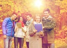 Groupe d'amis de sourire avec des comprimés en parc Image libre de droits