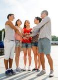 Groupe d'amis de sourire avec des mains sur le dessus dans la ville Image stock
