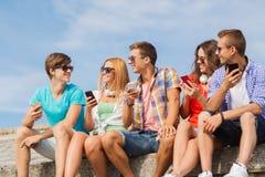 Groupe d'amis de sourire avec des smartphones dehors Photo stock