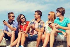 Groupe d'amis de sourire avec des smartphones dehors Photographie stock
