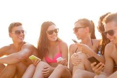 Groupe d'amis de sourire avec des smartphones sur la plage Image libre de droits