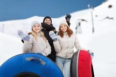 Groupe d'amis de sourire avec des tubes de neige Image libre de droits