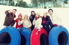 Groupe d'amis de sourire avec des tubes de neige Images libres de droits