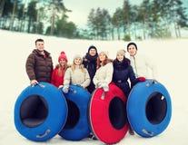 Groupe d'amis de sourire avec des tubes de neige Photographie stock libre de droits