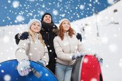 Groupe d'amis de sourire avec des tubes de neige Images stock