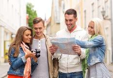 Groupe d'amis de sourire avec la carte et le photocamera Photo stock