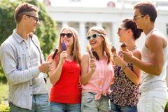 Groupe d'amis de sourire avec la crème glacée dehors Photographie stock