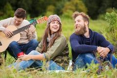 Groupe d'amis de sourire avec la guitare dehors Photographie stock libre de droits