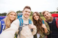 Groupe d'amis de sourire avec la hausse de sacs à dos Photos libres de droits