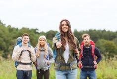 Groupe d'amis de sourire avec la hausse de sacs à dos Photo stock