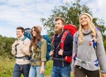 Groupe d'amis de sourire avec la hausse de sacs à dos Image stock