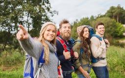 Groupe d'amis de sourire avec la hausse de sacs à dos Photographie stock