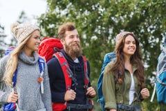 Groupe d'amis de sourire avec la hausse de sacs à dos Photo libre de droits