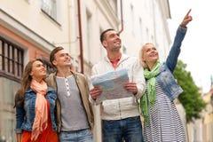 Groupe d'amis de sourire avec la ville l'explorant de carte Images libres de droits