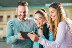 Groupe d'amis de sourire avec le comprimé numérique Photos stock