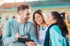 Groupe d'amis de sourire avec le comprimé numérique Photographie stock libre de droits