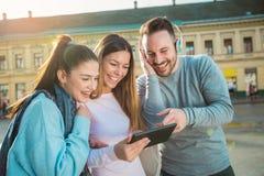 Groupe d'amis de sourire avec le comprimé numérique Image libre de droits